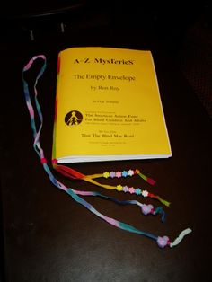 DYI bookmark for Braille books.  Made with shoe laces or thick yarn and beads to help hold the bookmark in place.  Made by Merry-Noel Chamberlain, TVI.  **visit pinterest.com/wonderbabyorg/ for more great activities for children with blindness.