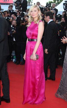 Kirsten Dunst apostó por el color escogiendo este rotundo vestido fucsia con cinturón negro de Christian Dior. Lo acompañó con joyas de Louis Vuitton y un clutch cuajado de piedras. En Festival de Cine de Cannes 2012