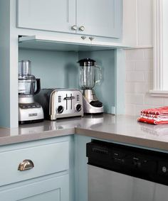 Soft blue keeps the 1950s charm alive in this kitchen, while serving as a streamlined counterpart to sleek hardware and modern appliances. | Photo: Casey Dunn | thisoldhouse.com kitchen appliance garage, appliances, 1950s, blue walls, small kitchen color ideas, kitchen colors, open kitchens, countertop, applianc garag