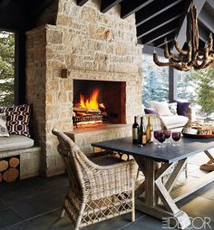 The covered porch of this Idaho home is paved in gray sandstone tiles with a driftwood chandelier from Mecox Gardens. The limestone fireplace is flanked by seating areas