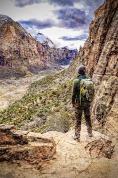Hiker on Angels Landing Trail which is a 5 mile trail that culminates on Zion National Park's iconic, dizzying ridge & offers stunning canyon views.