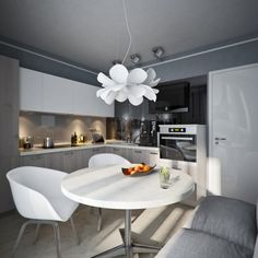 chic dining area equipped with round dining table, white dining chairs and flower-shaped pendant light