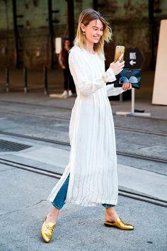 Street style look com maxi vestido branco sobre calça jeans e sapatos dourados.