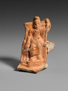 Terracotta lamp handle. Period: Imperial. Date: 2nd century A.D. Culture: Roman. Zeus Serapis, enthroned, holds a scepter in his left hand and rests his right hand on the head of Cerberos, the guard dog of Hades. Since the Roman Serapis is equated with Osiris, the Egyptian god of the Underworld, it seems appropriate to pair him with another representative of Hades, Cerberos. The association between the Greek god Zeus and the Egyptian god Serapis descends from Ptolemaic cult and highlights…