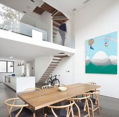 Concrete flooring continues from outside in to create a seamless transition between the living spaces and garden in this house, which are also connected by the 6.3-metre-high pivoting glass door.