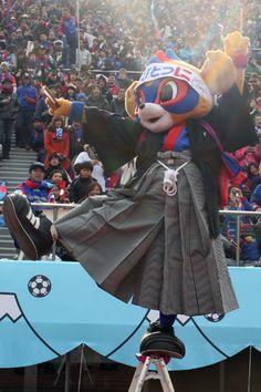 [ 第91回天皇杯 決勝 京都 vs F東京 ] 東京ドロンパがサポーターの前で音頭を取りながら脚立の上に立ち、バランスを取りながらTOKYOのKの字を表す。見事に決まるとサポーターから拍手喝さいが。   2012年1月1日(日):国立競技場
