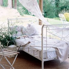 Ahhh....nothing says summer like an antique iron bed out of doors:) where you can lay out and read a book on a breezy summer day....