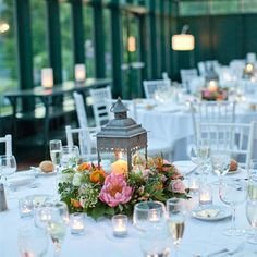 ~ Reception Décor ~  Style: Rustic ;  Item: Centerpiece ;  Palatte: Pink * Orange * Green ;  Recipe: Peonies, Ranunculuses, Latern, Candle ; Rustic lanterns were surrounded by lush florals and greenery on the white-clothed reception tables.