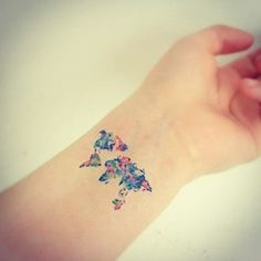 Watercolor world map tattoo on wrist