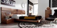Dormitorio con gran cabecero en madera y mesillas y mueble auxiliar también en madera