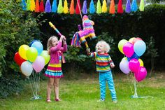 Kids playing with birthday pinata in decorated garden