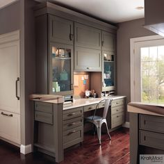 Sage and Mushroom finishes star in this timeless home office. The secret to the high-functioning space is the combination of drawers, cabinets and cubbies, which provide the perfect place for every office essential.