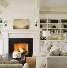 FIREPLACE: built-ins flanking simple white mantle with bumped out area extending to ceiling...or crowned off earlier.