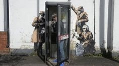 """The """"guerrilla artist"""" Banksy admits he painted a work of art depicting three spies """"snooping"""" on a telephone box in Cheltenham"""