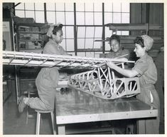 Three African American women in WWII era work clothes, constructing a wooden skeleton frame of what seems to be a scale aircraft. Anyone know more?