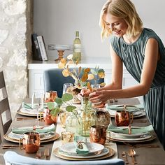 Woman decorating a table set with a eucalyptus stem White Dinnerware, Melamine Dinnerware, Business Furniture, Charger Plates, White Pumpkins, Dining Room Sets, Inspired Homes, Plate Sets, Moscow Mule Mugs