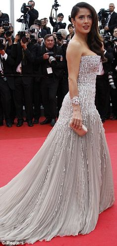 Stunning: Salma Hayek slipped into an off-white pleated dress as she lit up the red carpet this evening  Cannes