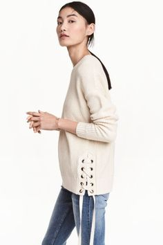 Knitted jumper with lacing: Knitted cotton jumper with lacing at the sides, dropped shoulders, long sleeves and ribbing around the neckline, cuffs and hem.