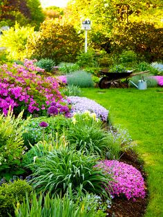 Use geometry to contrast or complement the flowerbed's curving borders repeat in the gentle edging of lawn. Plants chosen in similar hues...lavender, light purple, and fuchsia offer a soothing color for the garden. Love this garden!!