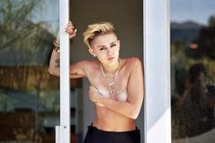Miley Cyrus topless holding breasts standing between glass door