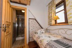 """""""Wiąz"""" to kameralna propozycja dla chcących prywatności: jednoosobowy pokój z łazienką. Pokój posiada podwójne łóżko, łazienkę, stolik i 1 krzesło."""