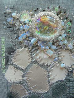 'Gleam': Fabric art based on photos of ice; created 2009  The shimmer of the appliqued pieces of salvaged gray satin coat lining fabric gives the piece its name. The flat AB glass cabochon focal is surrounded by moonstones, bugles, sequins, beads,   Size of embroidered area approx 6 inches square.   © 2015 Carol Walker.