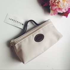 """LONGCHAMP 'Le Pliage' Pouchette longchamp 'le pliage' pouchette  embossed leather trim refines a durable, water-resistant nylon case accented with goldtone hardware.  † ivory beige color  † water-resistant lining † nylon with leather trim † 7.5""""W x 4""""H x 2.5""""D,  1"""" strap drop † new with tags   ✗ NO trades ✗ NO lowballing ✓ open to reasonable offers ✓ ask me to BUNDLE! Longchamp Bags Cosmetic Bags & Cases"""