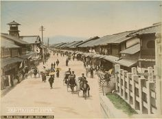 1890's, Kyoto. The entertainment district of Gion in Kyoto as seen from the steps of Yasaka Shrine. The street is flanked with a multitude of teahouses where customers could enjoy food, dance and music.