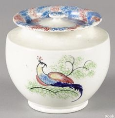 Pook & Pook 10/7/16 Lot: 131.   Estimate: $200 - 400. Realized: $3,120.  Description: Unusual spatter covered sugar with a red and blue rainbow rim and bird variant on body, 4 1/2'' h. Provenance: The Estate of Louis G. and Shirley F. Hecht, Baltimore, MD.  Condition: Three rim repairs.
