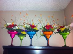 Fiesta Party Centerpieces: plastic margarita glasses filled with white sand and bright colored flowers.