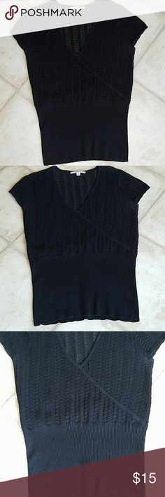 """PRE LOVED BLACK FAUX WRAP SWEATER TOP Faux wrap sweater top. This needs a cami underneath. PRE loved. Worn only once. Washed once on delicate, and hang dried. Excellent condition. I don't remember where I got this from. V-neck, short sleeves. 16.5"""" pit to pit. 24.5"""" from shoulder to hem. Material has stretch. The color is rich, and not faded. The pics where it looks faded were taken in a way so the texture was visible, because the last 8"""" of the bottom of this is ribbed. :) Tops"""