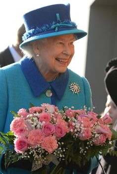 Queen Elizabeth II receives bouquets from children during her visit to The Factory Youth Zone in Manchester on 14.11.13.
