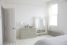 Painted floor, huge mirror, gray-green distressed dresser, white walls