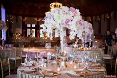 Lavender, white, and pink flowers on gold table setting and chiavari chairs.