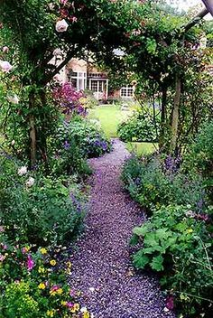 Love the way the plants spill over into the path and the climbing rose trellis to walk under.