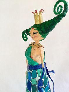 Margarida è la parte buona di Marange, una strega cattivissima , è tornata sulla terra per riparare alle sue malefatte. E verde perchè ancora porta addosso un pò della rabbia di Marange ;-). Se la porti a casa con te ti proteggerà dalle cattiverie , lascerà chiuso fuori tutto il male che