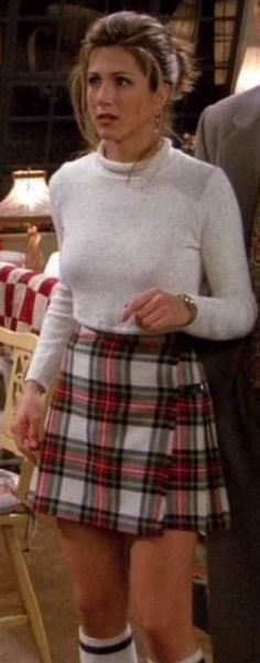 Jennifer Aniston in high-waisted plaid or tartan skirt with visible bra cups and straps and athletic socks. #vpl