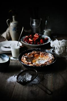 Dark and moody image of a Dutch baby pancake, for breakfast. Lighting: the image is side-lit, and photographer chose not to use a bounce on the right, and keep those shadows deep. Colour: yellows, oranges and reds, balanced with more neutral whites, gray and small pop of blue. Shallow depth of field, about 30-35 degree angle.