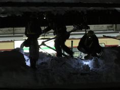 The worker who the overhead wire of the train is snapped for a heavy snow, and pushes on for the snow removing and repair work.