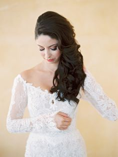"""""""Off-the-shoulder is such a romantic neckline, so you want to keep the hair very soft,"""" explains Temur. """"What's great about that is that you can keep it straight and sleek or soften it up with some waves or curls. It depends on the bride!"""" A side-swept style, like this one, feels impossibly romantic, especially with cascading curls."""