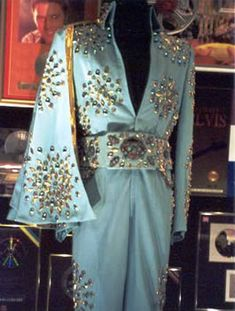"""Blue Pinwheel - No pictures nor footage of Elvis wearing this suit has surfaced. It has been on display at Graceland for a long time. Elvis possibly wore this suit during his 1973 January/February engagement, but the suit was never worn on tour. Judging by it's design, it could be considered as an """"upgraded"""" version on the 1971 """"Pinwheel's"""". The belt also has a slight resemblance to the belt Elvis wore with the """"Thunderbird"""" in 1972. It was a gift from the actor Jack Lord."""