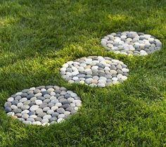 idée de chemin de jardin en pas japonais en rondelles de galets dans la pelouse
