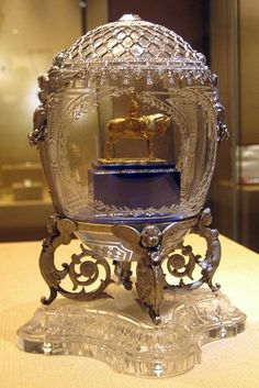 The Alexander III Equestrian Egg was ordered by Nikolay II from Faberge to his mother, a widow of Alexander III. The lower part of the egg serves as a platform for a gold model of a statue of Tsar Alexander III on horseback, standing on a nephrite base embellished with two rose-cut diamond bands, engraved with Fabergés signature, supported by cast platinum cherubs coiled into position on a base of crystal.It is currently held in the Kremlin Armoury Museum in Moscow.