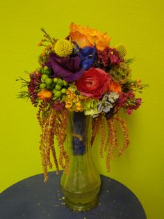 This rainbow bouquet uses both red and orange roses, purple lisianthus, bright blue delphinium, lavender stock, pink waxflower, green hypericum berries, scabiosa pods, and hanging amaranthus.  See more wedding bouquets, centerpieces, and more at www.jeffmartinsweddings.com