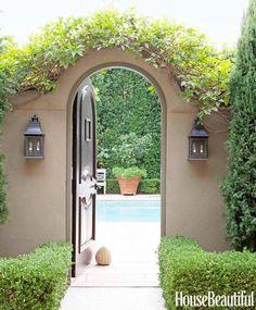 Taupe walls, brown door, dark grey light fixtures surrounded by green bushes