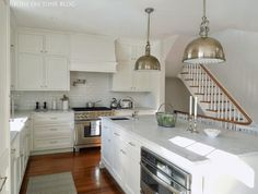 Lovely kitchen features white shaker cabinets paired with carrera marble countertops and a glazed ...