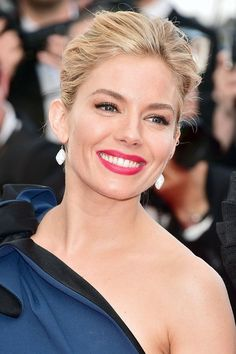At the Cannes Opening Ceremony, Sienna Miller wore her hair swept back into an up-do, offset by bold cherry-red lipstick.