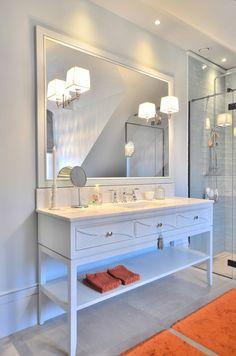 Elegant baderom på ben i lys blå farge. Innfelte skuffer med buede profiler og kryss over åpen hylle. Knotter i krom og eikefinér innvendig i skuffer. Benkeplate i Bianco Carrera marmor og Axor Montreux kran. Dekorative lamper montert på speil.