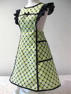 Perfect gift for Mothers Day. This cheerful apron features a design in shades of greens, white and black diamonds. The 2 large pockets can hold your recipes or maybe your cell phone. Inspired by a vintage pattern. Accented with black polka dot ruffles on the shoulders and black bias tape. The bodice is trimmed with black rick rack and a black bow. Ties at the waist. Neck straps button at the waist in back and can be adjusted. Straps can be crossed or straight in the back. Pinned down to fit…
