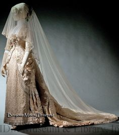 Wedding dress, Sharpless & Sons, Philadelphia, ca. 1879. This elaborately beaded and pleated wedding gown of brocaded satin has a train and a small padded bustle, both elements of everyday fashion at the time. Matching slippers of silk satin with glass beads have been preserved with the gown. FIDM